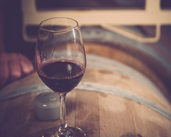 glass of wine on a wooden barrel