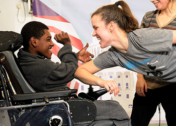 a boy in a wheelchair and a woman smiling at each other