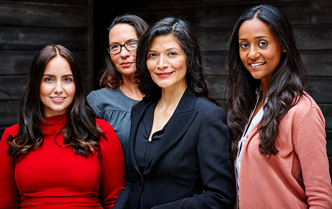 Four women of varying ages and ethnicities in business casual clothing