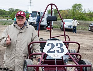 man standing next to a maroon kart from the front