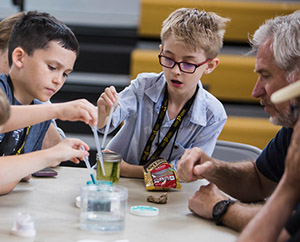Children doing a science experiment with an older man