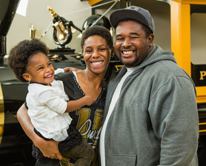 A smiling black family posing in front of the Boilermaker Special