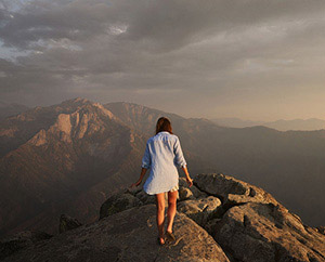 A woman walks on a mountain top at sunset